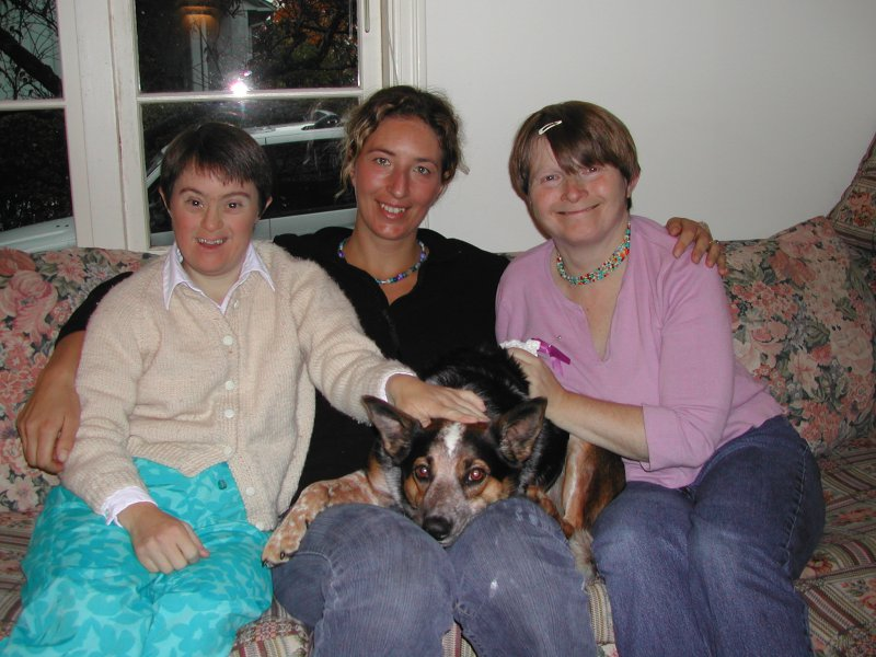 Three friends smiling, sitting together on the couch with their dog.